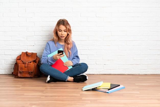 屋内の床に座っているピンクの髪のティーンエイジャーの学生女性がモバイルでメッセージを送信します
