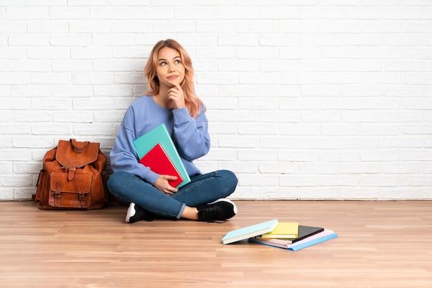 핑크 머리를 찾는 동안 아이디어를 생각 실내에서 바닥에 앉아 십 대 학생 여자