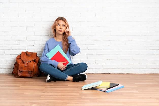 실내에서 아이디어를 생각에서 바닥에 앉아 분홍색 머리를 가진 십 대 학생 여자