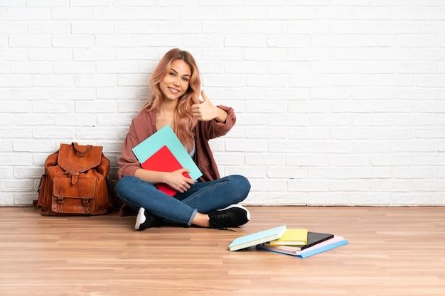 何か良いことが起こったので、親指を立てて屋内の床に座っているピンクの髪のティーンエイジャーの学生女性