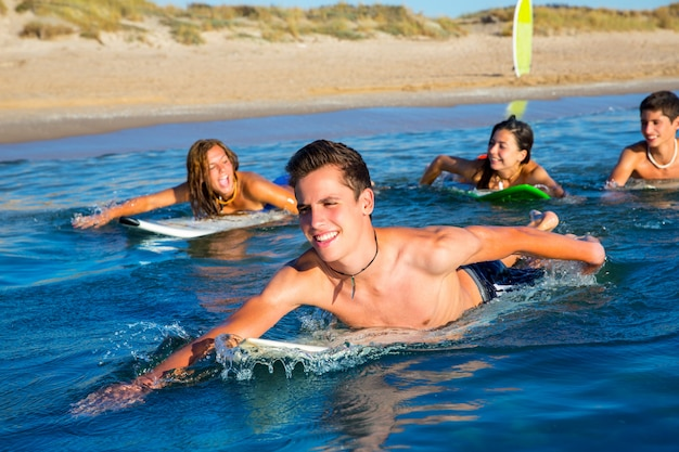 Teenager surfer boys and girls swimming ove surfboard