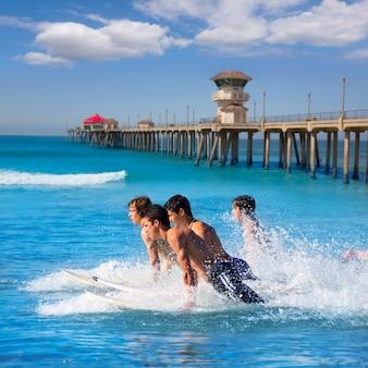 Teenager surfers running jumping on surfboards