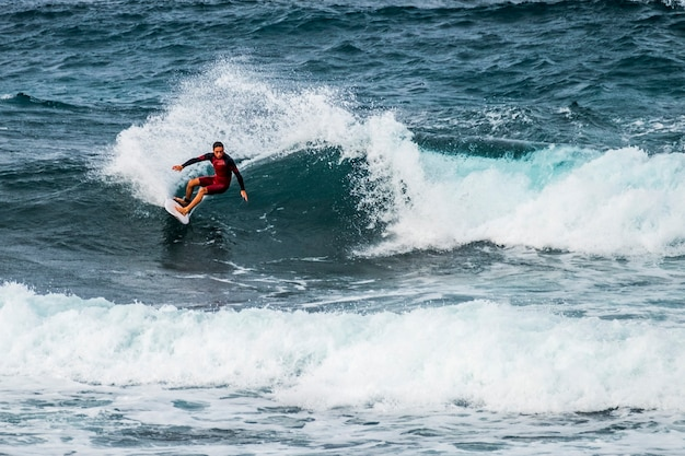 テネリフェプラヤデラスアメリカスの波でサーフィンするティーンエイジャー-赤いウェットスーツと美しく完璧な波-フリースタイルとトリックを行う