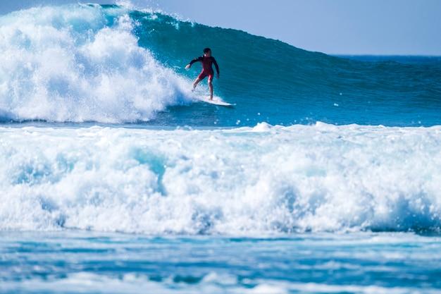テネリフェプラヤデラスアメリカスの波でサーフィンするティーンエイジャー-赤いウェットスーツと美しく完璧な波