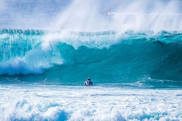 テネリフェプラヤデラスアメリカスの波でサーフィンするティーンエイジャー-白と黒のウェットスーツと美しく完璧な波