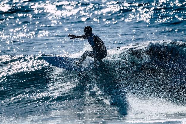 Подросток, занимающийся серфингом на волне на тенерифе, плайя-де-лас-америкас - белые и черные гидрокостюмы и красивая и маленькая волна