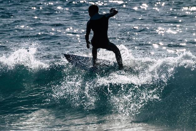 テネリフェプラヤデラスアメリカスの波でサーフィンするティーンエイジャー-白と黒のウェットスーツと美しくて小さな波