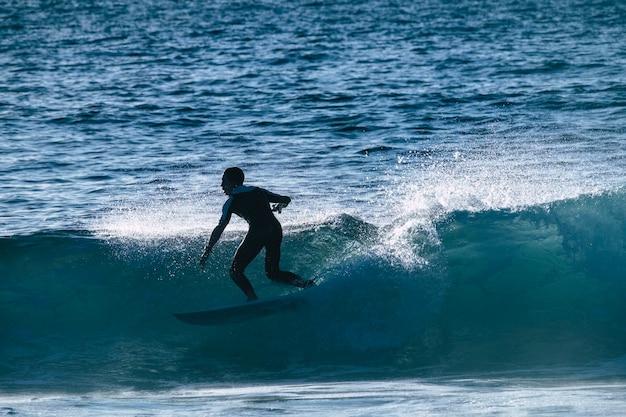 テネリフェプラヤデラスアメリカスの波でサーフィンするティーンエイジャー-白いウェットスーツと美しく完璧な波