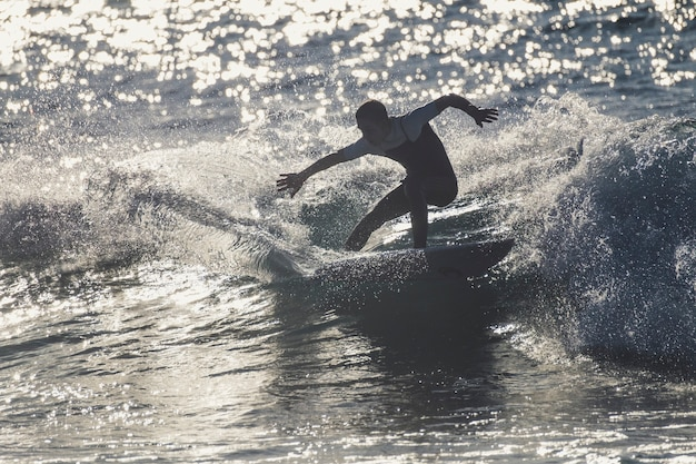 Подросток, занимающийся серфингом на волне на тенерифе, плайя-де-лас-америкас - белые гидрокостюмы и красивая и идеальная волна