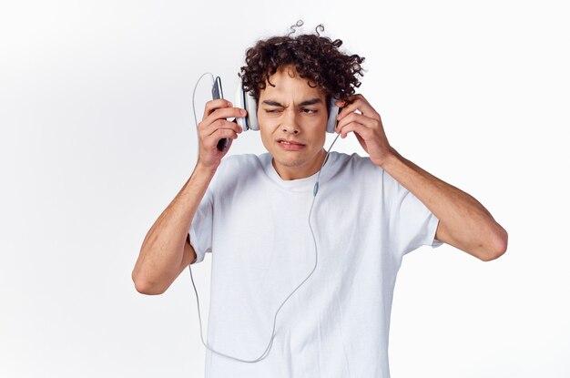 ティーンエイジャーのtシャツと明るい背景の新しいテクノロジーモデルのヘッドフォン