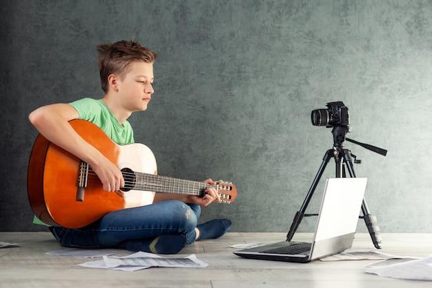 Подросток снимает видеоблог игры на домашней гитаре на камеру. молодой мальчик-подросток видеоблогера учится играть на гитаре онлайн в гостиной,