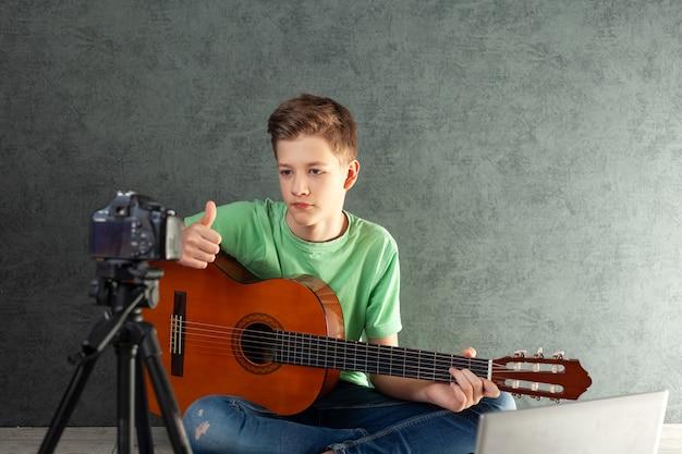 Подросток снимает видеоблог игры на домашней гитаре на камеру.