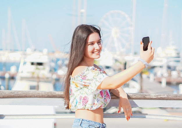 Teenager taking selfie at beach - young girl holding smartphone camera to take a picture of herself during her summer vacations