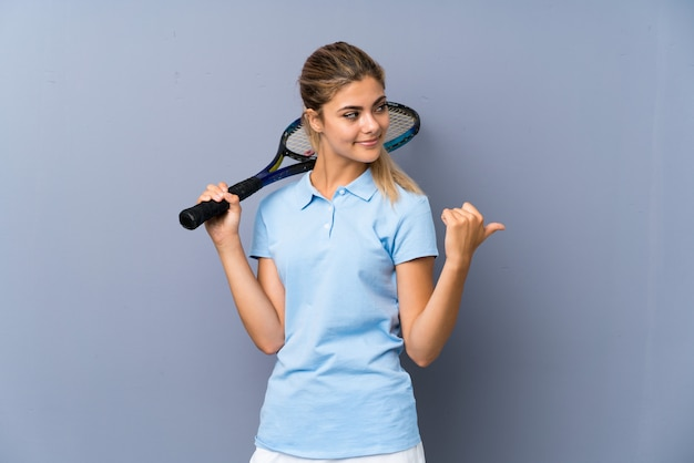 Teenager tennis player girl over grey wall pointing to the side to present a product