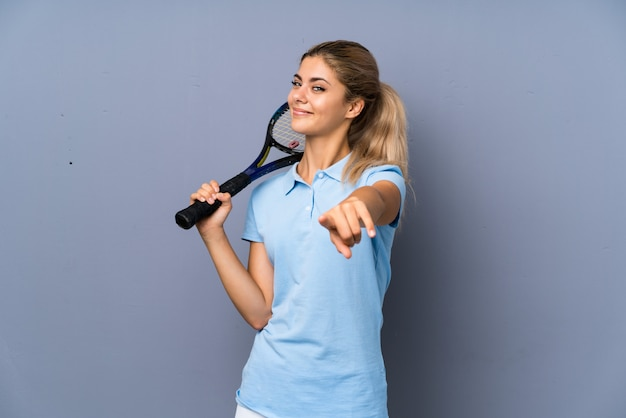 Teenager tennis player girl over grey wall points finger at you with a confident expression