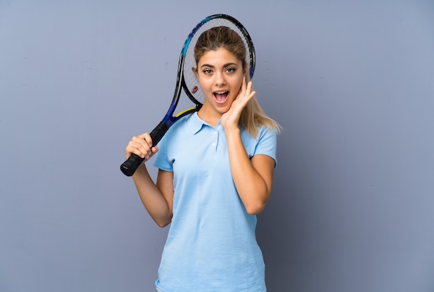 Teenager tennis player girl over grey wall with surprise and shocked facial expression
