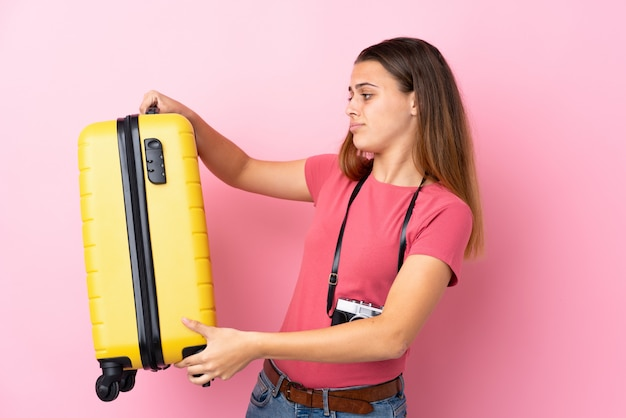 Teenager traveler girl holding a suitcase over isolated pink with sad expression