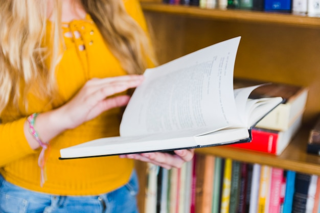 Teenager turning over book pages