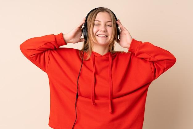 Teenager ukrainian woman isolated on beige space listening music