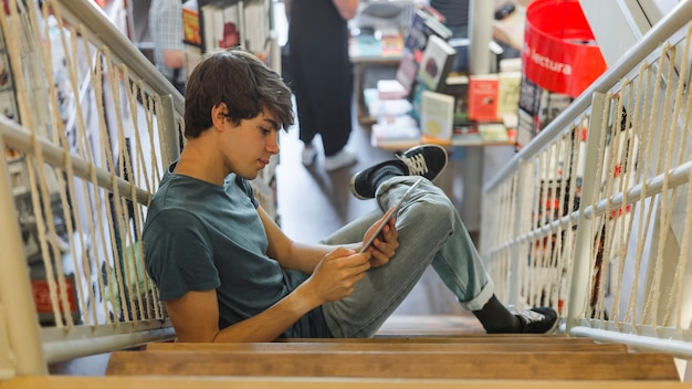 Teenager using tablet in bookstore