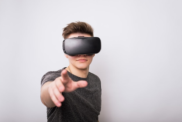 A teenager in a viar glasses pulls his hand to the screen. the virtual reality