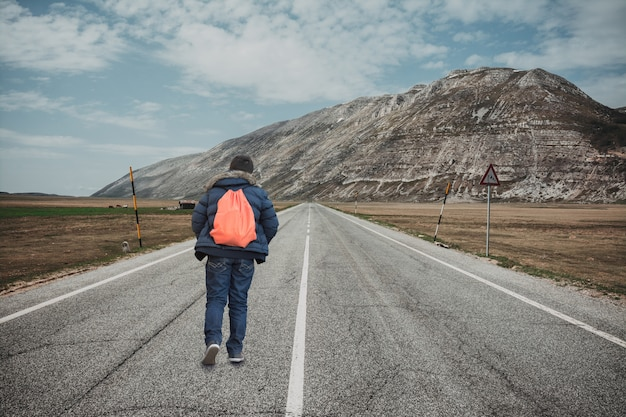 Teenager walking away on mountain road. concept of escape and adventure