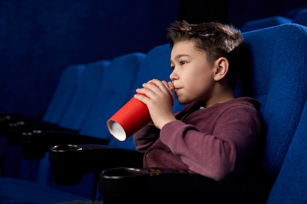 Teenager watching movie, drinking fizzy drink in cinema.