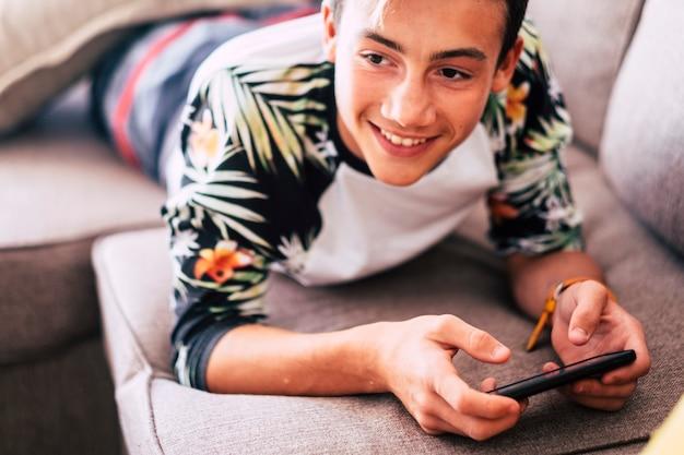 Подросток смотрит видео или играет в игры в смартфоне зимой, лежа на диване в гостиной дома -