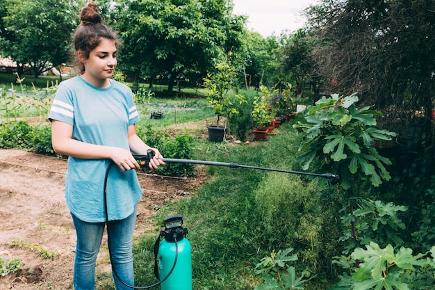 Teenager watering garden plants