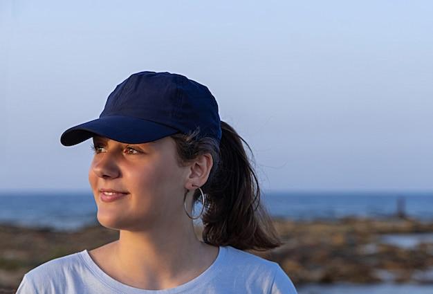 日没時に紺色の野球帽をかぶったティーンエイジャー。十代の少女の顔。キャップモックアップ