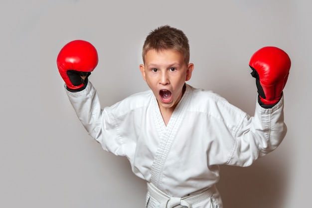 A teenager in a white kimono and gloves for hand-to-hand combat on a gray . doing sports.