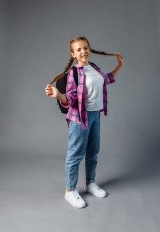 배낭을 든 십대. 귀여운 웃는 여학생. 어린 여학생이 배낭을 메고 있습니다. 긴 머리를 한 학생이 학교에 갑니다.