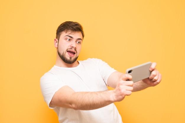 노란색에 스마트 폰에서 비디오 게임을 표현 적으로 재생하는 수염을 가진 십 대.