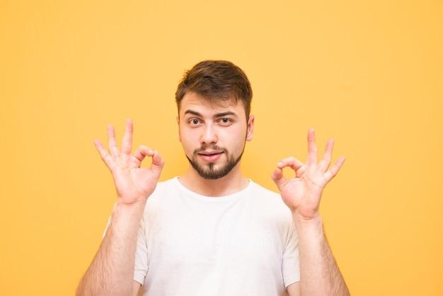Подросток с бородой на желтом, показывая жест ок