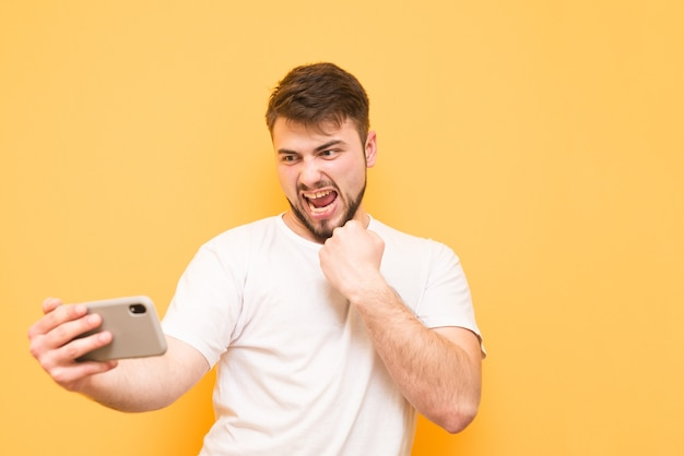 수염을 가진 십대는 스마트 폰에서 비디오 게임을하고 흰색 티셔츠를 입습니다.
