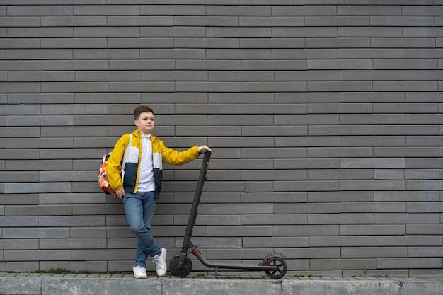Подросток с рюкзаком и электрическим самокатом на фоне кирпичной стены.