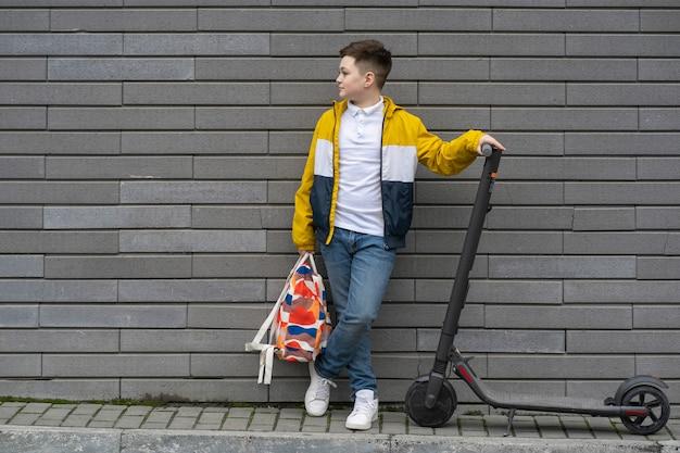 Подросток с рюкзаком и электросамокатом