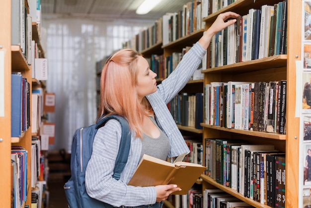 Teenager with backpack picking book from bookcase