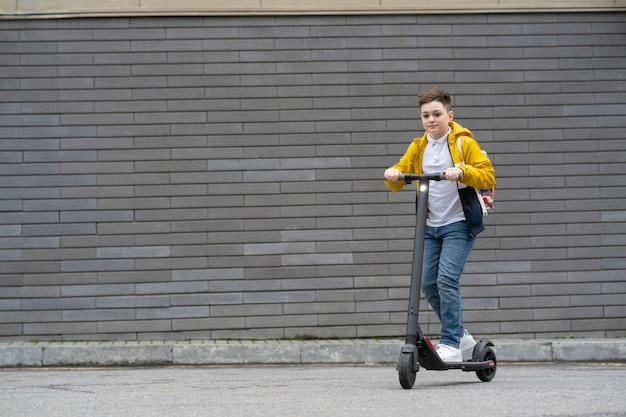 バックパックを持ったティーンエイジャーが電動スクーターに乗る