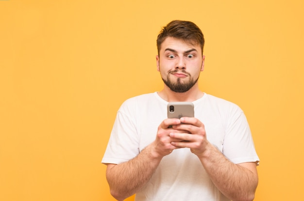 Teenager with a beard uses a smartphone on yellow, focuses on the screen and is surprised