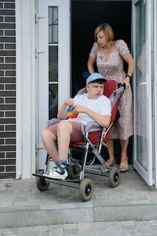 母親と散歩に行く特別な椅子に脳性麻痺のティーンエイジャー