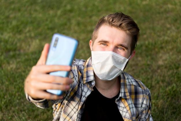 Selfieを取ってフェイスマスクを持つティーンエイジャー