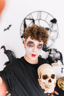 Teenager with fangs doing selfie with skull