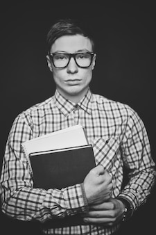 Teenager with glasses holding books