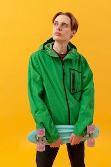 Подросток с зеленой курткой и скейтбордом