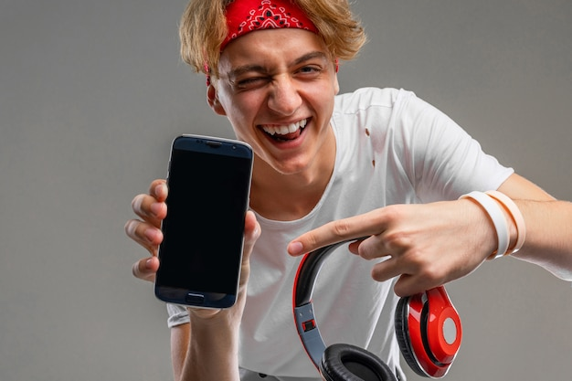 Teenager with headphones and phone, young man in a light t-shirt against a gray wall background