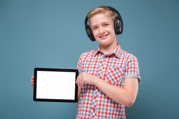 Teenager with headphones shows smartphone display, photo with space for text