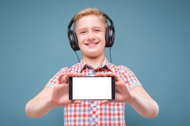 Teenager with headphones shows smartphone display