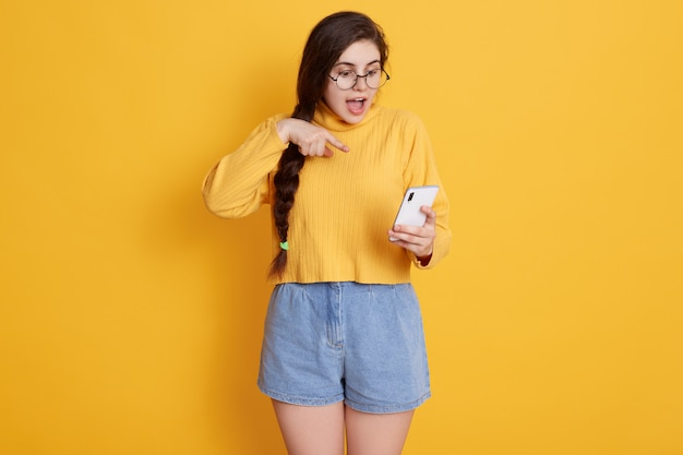 Teenager with opened mouth pointing at smart phone's screen which holding in hand