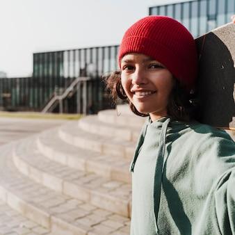 Подросток со скейтбордом в парке, делающий селфи